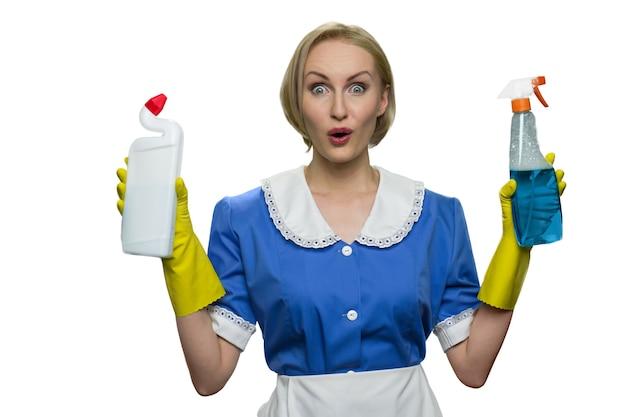 Femme de ménage surprise tenant un spray nettoyant et un désinfectant pour toilettes