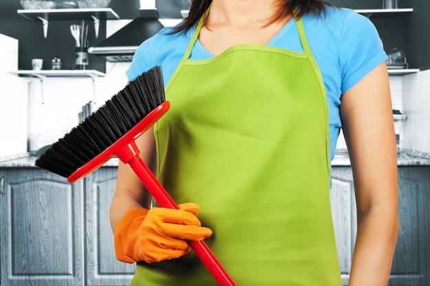 Femme de ménage avec un travail de maison de balai