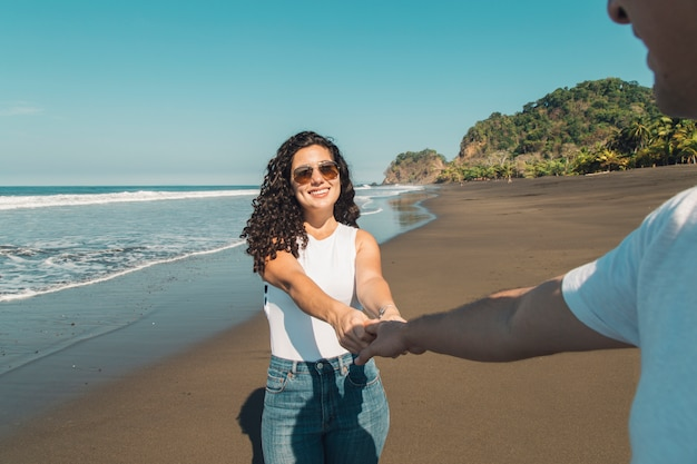 Femme menant l'homme sur la plage