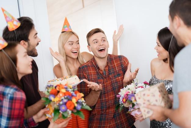 Une femme mène à la fête surprise de l'homme. anniversaire garçon sourit.