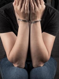 Une femme menottée a couvert son visage et regrette le crime.