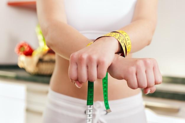 Femme menottée par un ruban à mesurer - symbole du trouble de l'alimentation
