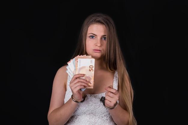 Femme menottes aux poignets avec des billets en euros isolés sur fond noir
