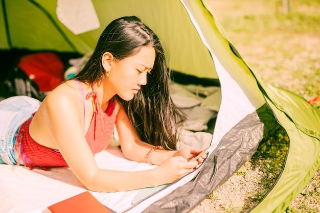 Femme, mensonge, dans, tente, à, téléphone portable