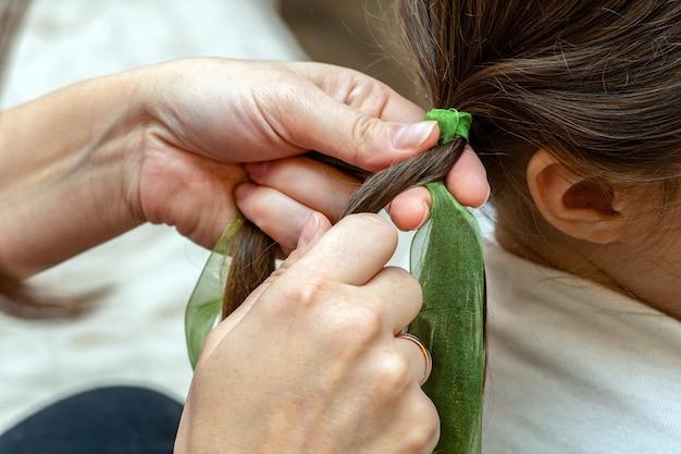 Femme, mère tisse des tresses sur des cheveux de fille avec des rubans de couleur