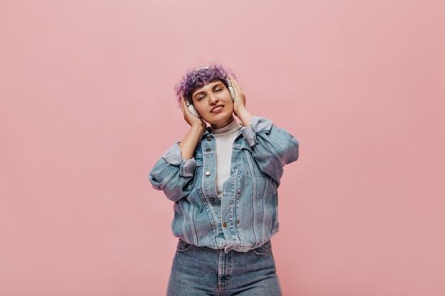 Une femme merveilleuse en jeans cool avec des cheveux bouclés lilas apprécie la musique. jolie femme en casque blanc posant.