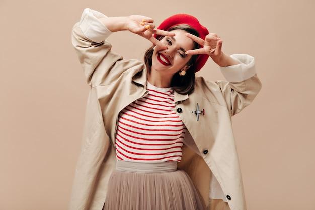 Femme merveilleuse positive en tranchée et béret rouge montrant des signes de paix sur fond isolé beige. belle dame dans des vêtements élégants sourit.