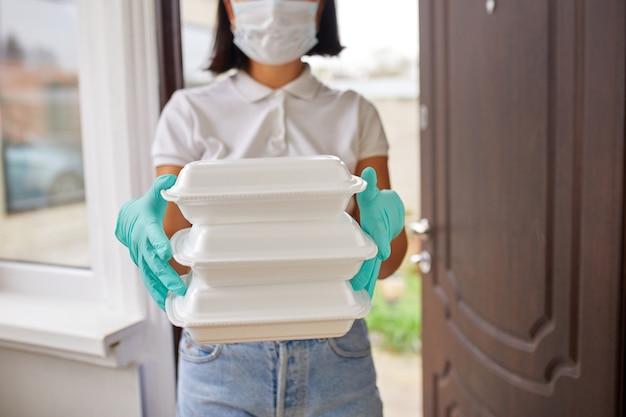 Une femme de messagerie tient une boîte de nourriture, un service de livraison, des restaurants à emporter livraison de nourriture à domicile, restez à la maison en toute sécurité contre l'épidémie de coronavirus covid-19, service de livraison en quarantaine.