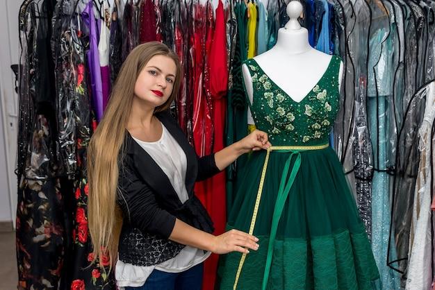 Femme mesurant la belle robe de soirée avec mètre