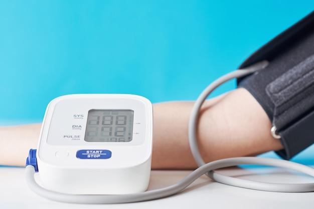 Femme mesurant la pression artérielle avec moniteur de pression numérique