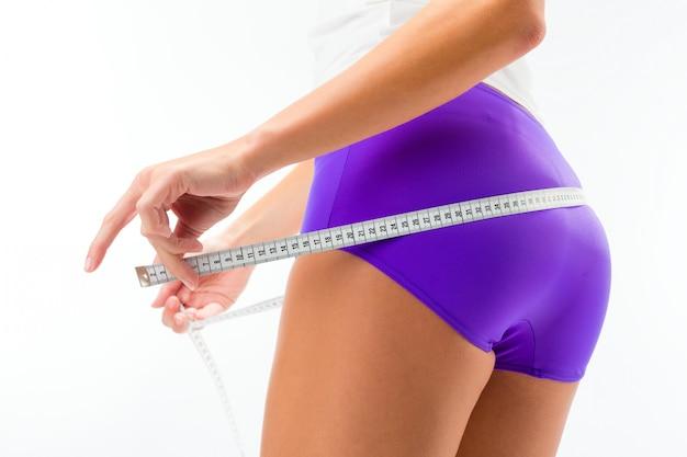 Femme mesurant sa hanche avec du ruban adhésif