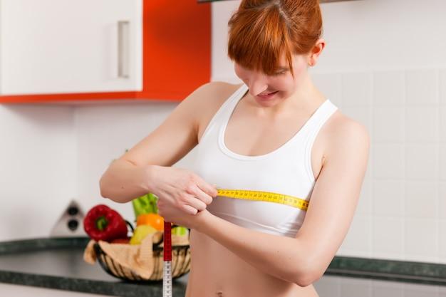 Femme mesurant sa poitrine avec du ruban adhésif