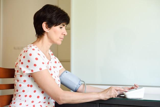 Femme mesurant sa propre pression artérielle à la maison.