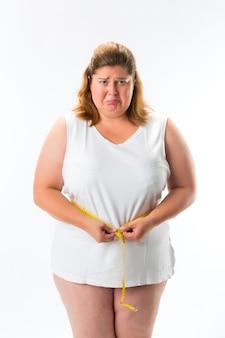 Femme mesurant sa taille avec du ruban adhésif