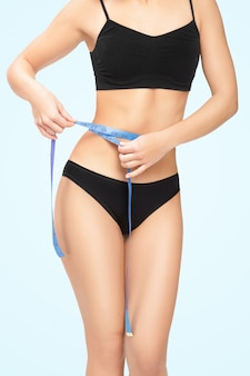 Femme mesurant sa taille avec du ruban de mesure bleu
