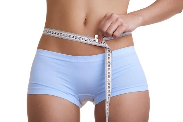 Femme mesurant sa taille isolé sur fond blanc