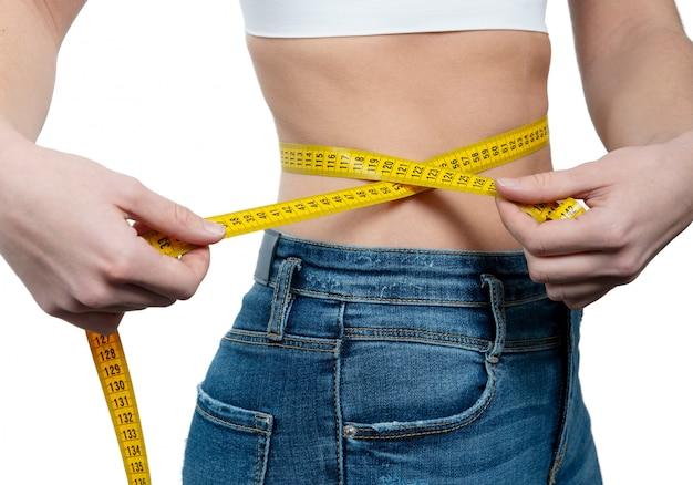 Femme mesurant sa taille avec un ruban à mesurer jaune