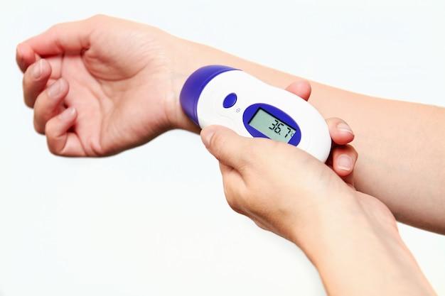 Femme mesurant sa température avec un thermomètre infrarouge
