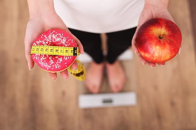Femme mesurant son poids sur une balance tenant un beignet et une pomme.