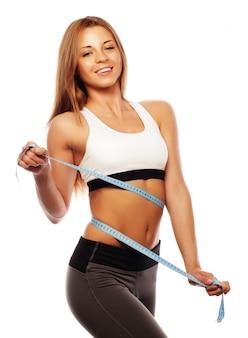 Femme mesurant son tour de taille. corps mince parfait. isolé sur blanc.