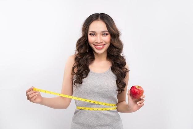 Femme mesurant son tour de taille et tenant une pomme. concept de perte de poids.