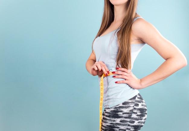 Femme mesurant la taille avec du ruban adhésif