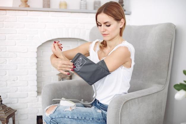 Une femme mesure la pression à la maison