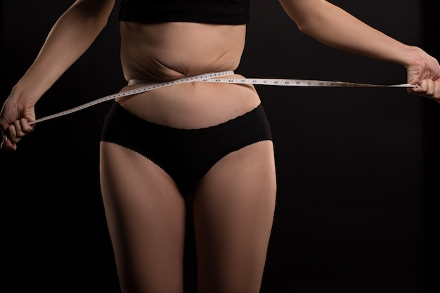 Femme mesure sa taille avec du ruban adhésif