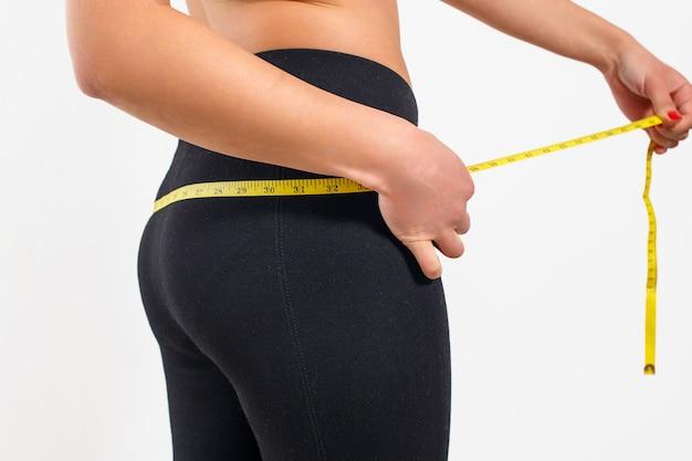 La femme mesure le volume de son bassin avec un ruban centimétrique.