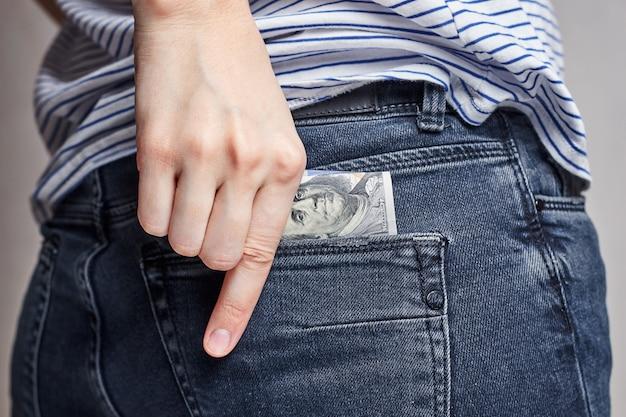 Femme met de l'argent dans sa poche arrière d'un jean