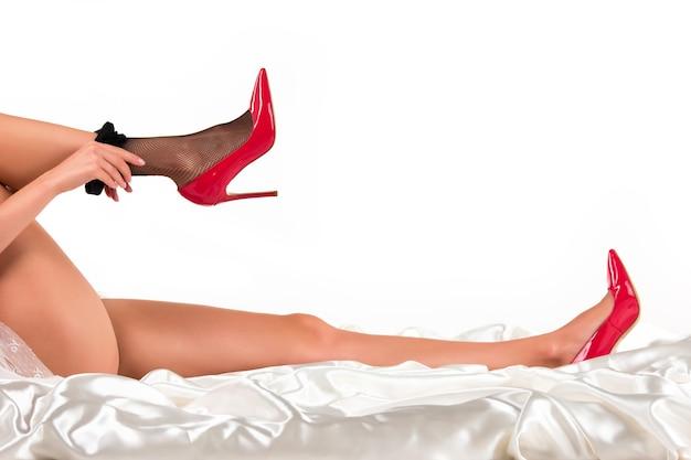 La femme met des bas. jambes en talons allongés. vous ne pouvez pas résister à la séduction. jeune et sexy.