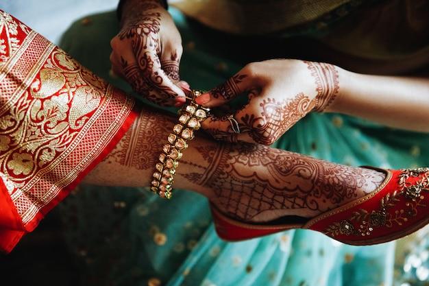Femme met le bracelet sur la jambe de la mariée hindoue