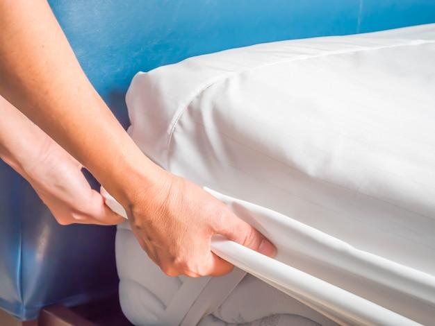 La femme met la couverture de lit ou la dépose pour le nettoyage