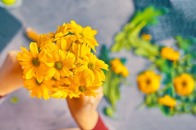 Femme met des fleurs de chrysanthème jaune dans un vase en verre transparent sur la table du grenier