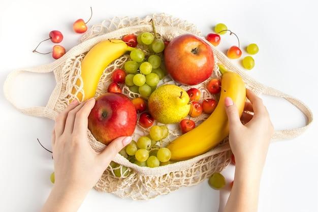 Une femme met des fruits mûrs dans un sac en filet écologique pour faire du shopping les mains des femmes tiennent un sac en coton