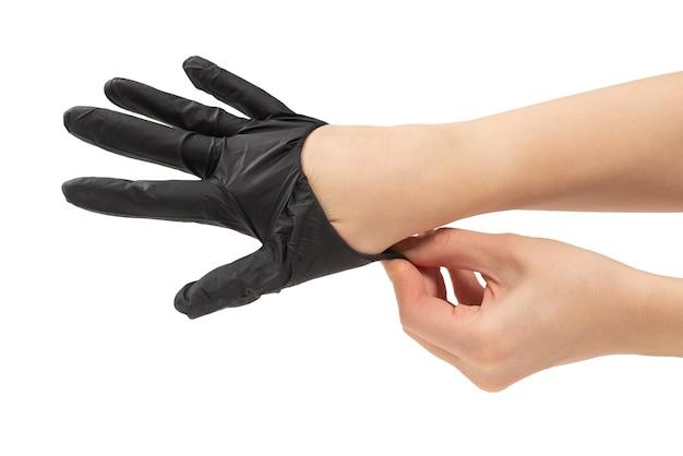 Femme met des gants en caoutchouc noir. isolé sur blanc.