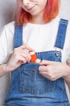 Une femme met un inhalateur dans sa poche pour traiter l'asthme. journée mondiale de l'asthme. concept de soins d'allergie