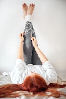 Une femme met des leggings en laine gris chaud, les jambes des femmes en leggings d'hiver