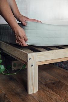 Une femme met un matelas sur le lit ou reporte le processus de nettoyage