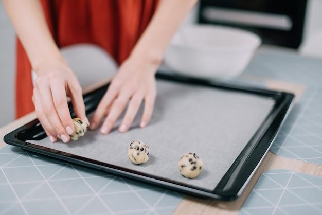 Femme met sur une plaque à pâtisserie biscuits crus avant la cuisson dans la cuisine