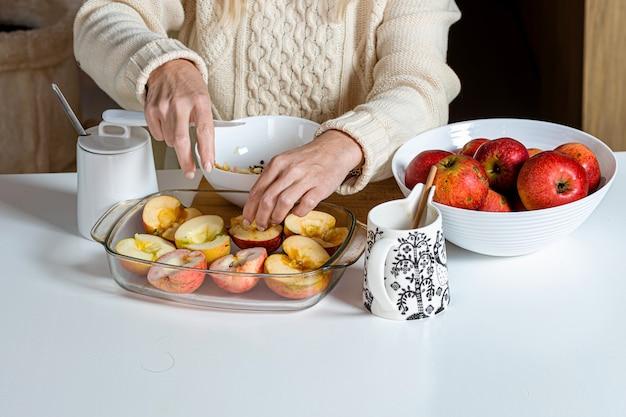 Femme met les pommes coupées à la main dans un bol en verre et les prépare pour la cuisson, le concept de cuisson maison pour les vacances