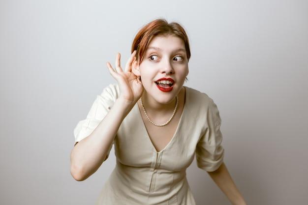 La femme met sa main à son oreille