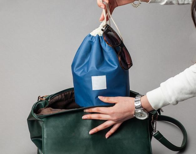 Femme met le sac de cosmétiques dans son sac féminin