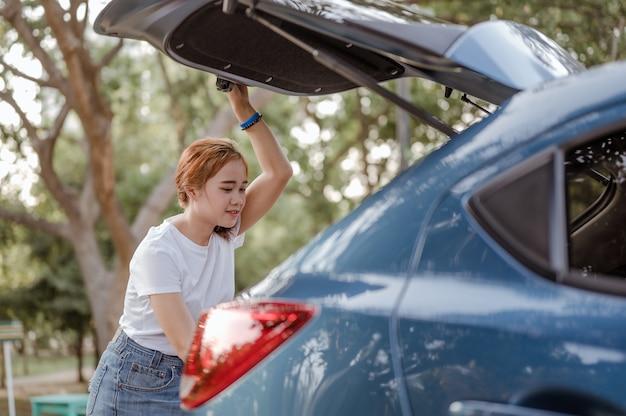 Une femme met un sac dans le coffre d'une voiture bleue pour partir en vacances voyage et vacances