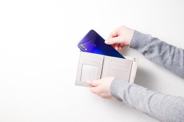 Femme met le smartphone dans le portefeuille
