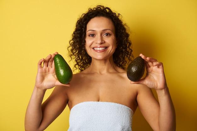 Une femme métisse aux cheveux bouclés tenant deux fruits mûrs d'avocat et souriant avec sourire à pleines dents, isolé