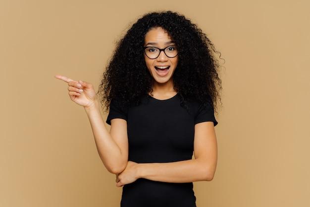 Une femme métisse brune pointe de côté avec l'index, a une expression curieuse et heureuse