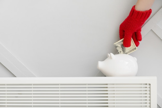 Femme mettant de l'argent dans la tirelire sur le radiateur. concept de saison de chauffage
