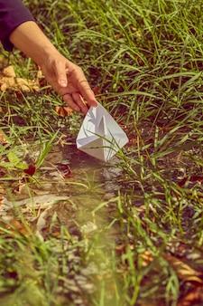 Femme mettant un bateau en origami dans l'eau.