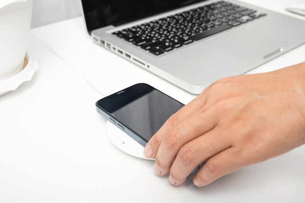 Femme mettant la batterie de charge du smartphone avec un chargeur sans fil près d'un ordinateur portable